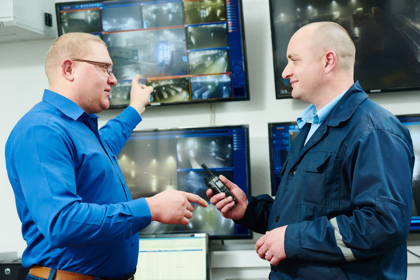 36953692 - security executive chief discussing activity with worker in front of video monitoring surveillance security system
